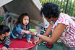 Education preschool outside at playground 3-4 year olds girl showing female teacher a leaf she picked up horizontal