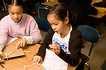 Education elementary Grade 3 science classroom two female students doing experiment on sound production horizontal