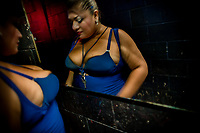 A Salvadoran sex worker checks herself out in the mirror in the backstage of a sex club in San Salvador, El Salvador, 13 November 2016. Sex workers' task in the club is to be an entertaining and seductive companion. Performing erotic dance on the pole they make the customers stay as long as possible and buy relatively expensive alcoholic beverages from which they have a certain share. Sex workers are not obliged to have sexual intercourse with the club customers, they decide themselves, usually according to their current economic situation.
