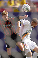 The MetroStars' Chris Leitch and the Galaxy's Alejandro Moreno go for a header as seen through the net. The LA Galaxy were defeated by the NY/NJ MetroStars 2 to 1 at Giant's Stadium, East Rutherford, NJ, on June 19, 2004.