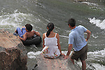 Couple watching boy tubing on Boulder Creek, Boulder, Colorado. .  John offers private photo tours in Denver, Boulder and throughout Colorado. Year-round.
