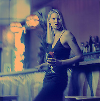 Woman with drink at bar<br />
