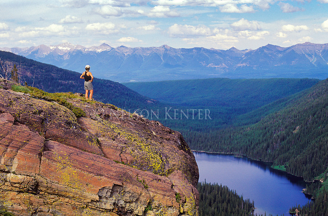 A hiker above Glacier Lake in the Seeley Swan Valley looks out toward the Swan Mountain Range in Montana