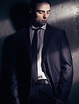 Artistic expressive portrait of a young man wearing a business suit standing looking down in dim dramatic light Image © MaximImages, License at https://www.maximimages.com