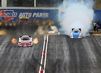 Feb 22, 2014; Chandler, AZ, USA; NHRA funny car driver Tony Pedregon (left) races down the track as Terry Haddock smokes the tires during qualifying for the Carquest Auto Parts Nationals at Wild Horse Pass Motorsports Park. Mandatory Credit: Mark J. Rebilas-USA TODAY Sports