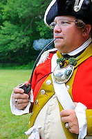 Captain of His Majesty's Northumberland Fusiliers 5th Regiment of Foote, wearing silver gorget at neck to indicate on-duty status, smokes a briar pipe while contemplating battle strategy during a Revolutionary War reenactment at the Nathan Hale Homestead, Coventry, Connecticut, USA...
