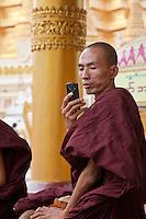 Myanmar, Burma.  Shwedagon Pagoda, Yangon, Rangoon.  Buddhist Monk with Cell Phone.