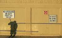 A poll workers shadow is cast onto a building wall in early morning light at Virginia Beach, Va.