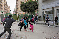 Young woman running along a back street near Tahrir Square during clashes between pro and anti government protesters. Throughout Friday, 4 February, anti government protesters protected their positions from pro Mubarak supporters around Tahrir square, the scene of heavy clashes between pro and anti government protesters. Continued anti-government protests take place in Cairo calling for President Mubarak to stand down. After dissolving the government and allowing for talks with opposition parties Mubarak still refuses to step down from power...