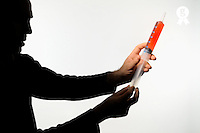 Man's silhouette holding  a  big syringe (Licence this image exclusively with Getty: http://www.gettyimages.com/detail/82406558 )