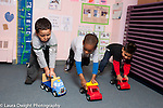 Education Preschool 4 year olds three boys playing game racing toy vehicles they are pushing in front of them