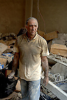 Local view the destruction in the Muawwad district of South Beirut after a night of Israeli Bombing. Mr Marwan Osseiran and his teenage son Nazir attempt to salvage goods from his storage unit where he kept sports good for his shop.
