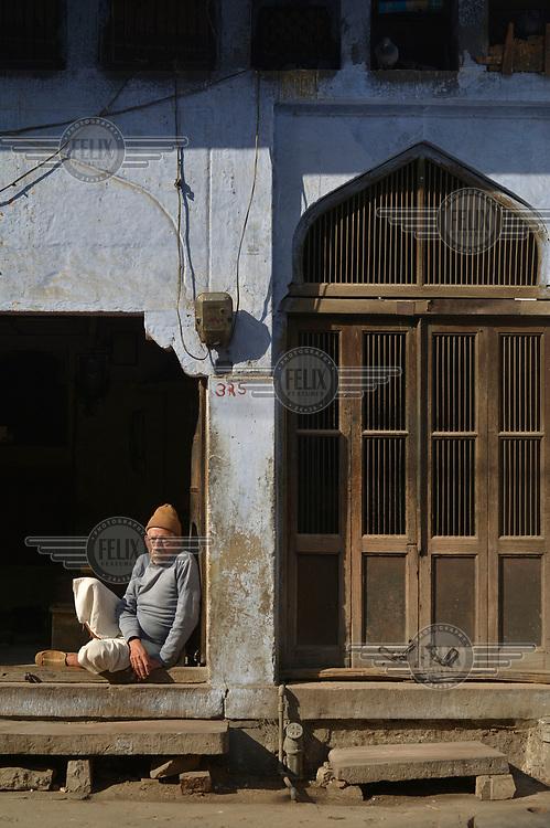 An elderly man sitting in an ornate doorway.