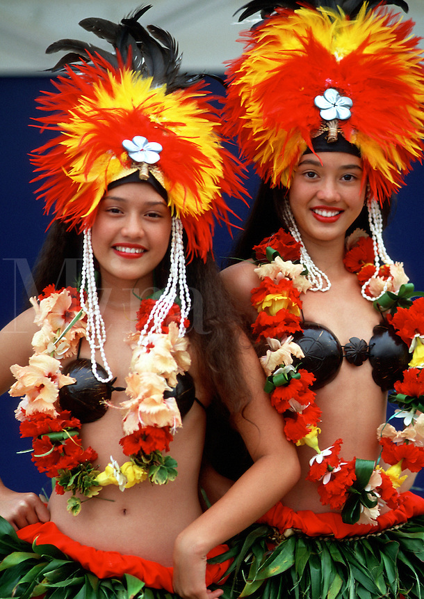 Portrait of smiling Polynesian dancers in colorful feathered headdress, leis and grass skirts. Bora Bora, Tahiti.