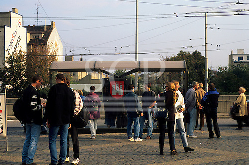 Bratislava, Slovakia: people at a trolley bus stop with the three tower castle motif of the city.