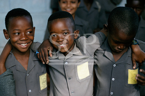 Lusaka, Zambia; three smiling boys wearing uniform shirts of the Jacaranda school.