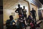 AGADEZ, NIGER — <br /> A group of migrants from Cameroon prepares to settle for the night a the bus station in Agadez, Niger. They were retuning from Arlit, a city north of Agadez which is situated in the middle of the Sahara desert. This group was traveling north with a smuggler in their attempt to reach Italy through Libya. As they approached Arliz, they ran into a police check point. They were promptly turned back after the police stole all their money and threatened to keep their travel documents if they didn't turn back. Without a dime to their name, they were forced to sleep on the Agadez bus station along dozens of other migrants before figuring out their next move.