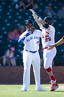 Surprise Saguaros second baseman Andy Young (29), of the St. Louis Cardinals organization, is congratulated by Vladimir Guerrero Jr. (27) after scoring a run during an Arizona Fall League game against the Salt River Rafters on October 9, 2018 at Surprise Stadium in Surprise, Arizona. Salt River defeated Surprise 10-8. (Zachary Lucy/Four Seam Images)