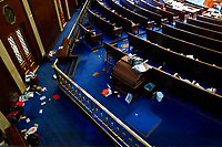 Papers and other materials litter the chamber after House were evacuated as protesters try to break into the House Chamber at the U.S. Capitol on Wednesday, Jan. 6, 2021, in Washington. (AP Photo/Andrew Harnik)