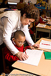 Parochial School Bronx New York  Kindergarten female teacher working with child on writing assignment holding and  guiding his hand vertical