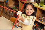 Education preschool 3-4 year olds girl talking to herself as she makes construction from sticks and cubes