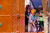 Colorful group of Indian children having fun and playing with color powder toys, during the Holi celebration in Mathura Uttar Pradesh, India