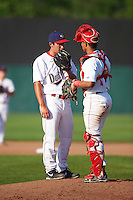 Auburn Doubledays relief pitcher Russell Harmening (29) talks with catcher Luis Vilorio (4) during a game against the Williamsport Crosscutters on June 26, 2016 at Falcon Park in Auburn, New York.  Auburn defeated Williamsport 3-1.  (Mike Janes/Four Seam Images)