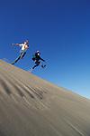 Two young men jumping off sand dune ridge; Oregon Dunes National Recreation Area, Umpqua Dunes section, Oregon coast.