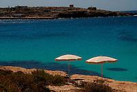 Lampedusa / Italia.Gli operatori turistici si lamentano della mancanza di turisti e danno spesso la colpa all'arrivo dei barconi di immigrati. Sullo sfondo il molo commerciale dove arrivano le carrette del mare con i migranti provenienti da Libia e Tunisia..Foto Livio Senigalliesi