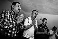 Colombian believers pray during the religious healing ceremony performed at a house church in Bogota, Colombia, 28 January 2013. Hundreds of Christian belivers, joined in nameless groups, gather every week in unmarked home churches dispersed in the city outskirts, to carry out prayers of liberation and exorcism. Community members and their religious activities are usually conducted by a charismatic pastor or preacher. Using either non-contactive methods (reading religous formulas from bible, displaying Christian symbols and icons) or rough body-pressure-points techniques and forced burping, a leading pastor commands the supposed evil spirit, which is generally believed to come from witchcraft, to depart a person's mind and body. The demon's expulsion often consists of multiple rites and may last for several months.