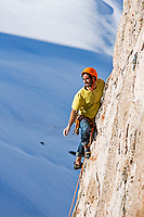 Lucho Birkner climbs some delicate and broken rock at one of the Los Monjes Blancos towers; Valle des los Condores, Chile