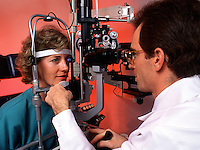 A male optometrist performs an eye exam on a female patient.