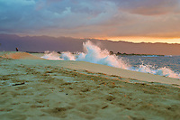 Waves crash on the beach at Ke'iki beach on the north shore of Oahu. Clouds over the Waianae mountains turn gold in the sunset light.