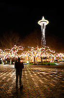 Nighttime scene of man standing on walkway in Seattle Center decorated with Christmas lights below Seattle Space Needle, Seattle Center, Seattle, Washington, US