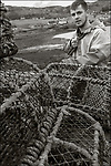 Isle of Skye, Scotland:<br /> On the wharf of Uig, a lobster fisherman mends his traps and lines. Trotternish penninsula
