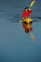 Single hispanic female kayaking on lake.