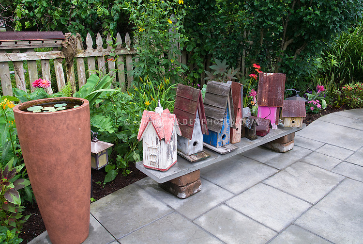 Variety of pretty and interesting birdhouses on bench, in lots of colors and shapes, with tall little water garden, picket fence, perennials and annual tropical looking garden bed, and stone patio, trees.
