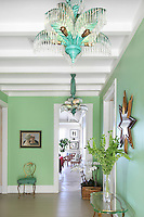 Old Hollywood glamour is brought into this mint green hallway with a pair of turquoise metal chandeliers in the shape of palm leaves with crystal drops