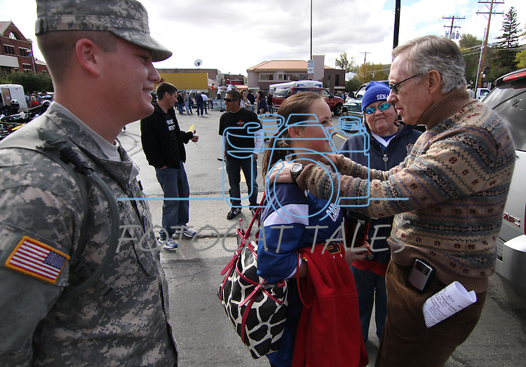National Army Guard Pvt. Austin Seder looks on as Senate Majority Leader Harry Reid talks with Seder's fiance Natalie Cave and her mother Patsy Cave during Saturday's Nevada Day festivities in Carson City, Nev. .Photo by Cathleen Allison