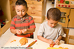 Preschool ages 3-5 two boys playing with play dough separately side by side horizontal