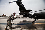 """A soldier washes down a Blackhawk during routine maintenance. Scenes from the medical evacuations of wounded Americans, Canadians, and Afghan civilians and soldiers being flown by Charlie Co. 6th Battalion 101st Aviation Regiment of the 101st Airborne Division. Charlie Co. - which flies under the call-sign """"Shadow Dustoff"""" - flies into rush the wounded to medical care out of bases scattered across Oruzgan, Kandahar, and Helmand Provinces in the Afghan south. These images were taken of missions flown out of Kandahar Airfield in Kandahar Province and Camp Dwyer in Helmand Province."""