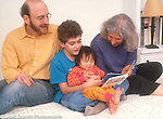 19 month old toddler girl with parents and brother, age 9, reading board book, adopted by US family from Vietnam as an infant