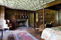 A 16th/17th century panelled bedroom with wide floorboards and a stone fireplace