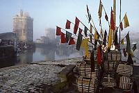 Europe/France/Poitou-Charentes/17/Charente-Maritime/La Rochelle : Les tours du  vieux port , Tour Saint-Nicolas et Tour de la Chaine , et les fanions et les casiers des caseyeurs  pour la pêche aux crustacés