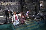 Holywell Pilgrimage on the feast day of  St Winefride. Holywell Flintshire Wales. Disabled woman  enters healing spring water, in hope of a cure. 1990s. <br /> St Winifred or Saint Winefride was a 7th-century Welsh Christian  woman, around whom many historical legends have formed. A healing spring at the traditional site of her death is now a shrine and pilgrimage site called St Winefrifdes Well,  known as the Lourdes of Wales.