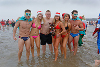 Pictured: Young men and women in bikinis and in festive fancy dress costumes run to the freezing cold see. Tuesday 25 December 2018<br /> Re: Hundreds of people take part in this year's Porthcawl Christmas Swim in south Wales, UK.