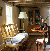 A painted yellow Swedish sofa from 1760 and a dresser in the living room