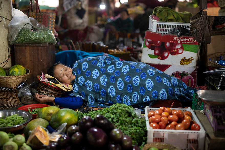 India - Manipur - Imphal - A vendor takes a nap on her stall during the day. Several women who work there don't have the cenessity to work but they enjoy keeping busy, being financial independent and spending time far from home and in the company of other women.