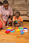 Three year old boy at home with father learning to do inter-connecting gear puzzle with him