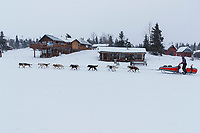 Victoria Hardwick is the last musher to leave the Rainy Pass checkpoint on Puntilla Lake and passes some of the Perrins Rainy Pass lodge buildings as a heavy snow falls in the morning during the 2019 Iditarod on Tuesday, March 5th 2019.<br /> <br /> Photo by Jeff Schultz/  (C) 2019  ALL RIGHTS RESERVED